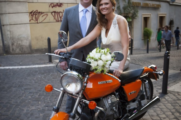 happy married couple on a motorbike in rome